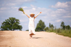 Women on country road with flowers Royalty Free Stock Images