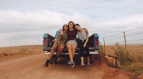 Women on a country side road trip. Portrait of three young female friends sitting at the back of a pickup truck parked on a country road. Group of women on a Stock Images