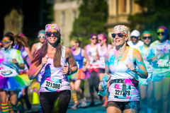 Women couple runs the Color Vibe 5K race. Color Vibe is a fun un-timed event with no winners or prizes where runners are showered with colored powder along the Royalty Free Stock Photos