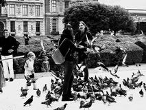 Women covered with pigeons Royalty Free Stock Image