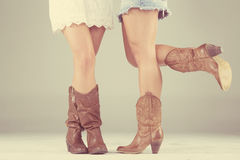 Women with cowboy boots. The legs of two women wearing cowboy boots royalty free stock photo