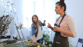 Women create garlands of flowers using blossoms and metal wire. stock video