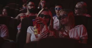 Women crying in cinema. Medium close-up of a woman crying while watching a sad movie in a cinema stock footage