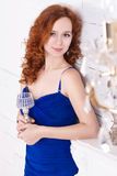Women with crystal glass. Young red-haired woman in a blue dress stands under a crystal chandelier and smiling. She is holding a crystal glass stock image