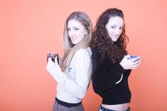 Women with cups. Young women back to back holding cups, smiling, portrait Stock Photography