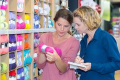 Women customer choosing various yarn in sewing store. Choosing royalty free stock photography
