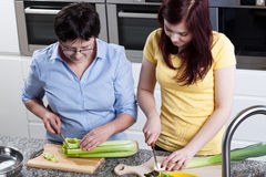 Women cutting celery and leek Royalty Free Stock Photos