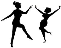 Women dancing in silhouette. Women dancing one is barefoot and one is in heels Stock Photography