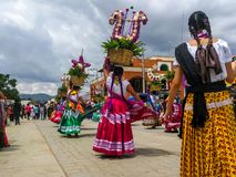 Women dancing through the streets with offerings at the Guelaguetza celebration. stock image
