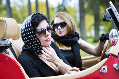 Women with dark glasses adjust spotted scarf Royalty Free Stock Image