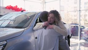 Women Day gift car, guy gives new vehicle to smiling girl which happy hugs and shows keys at auto showroom. Women Day gift car, loving guy gives new vehicle to stock video