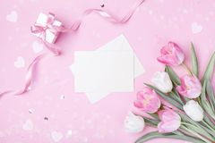Women Day, Mother day background with envelope, gift box and beautiful spring tulip flowers on pastel pink desk. Flat lay. Style royalty free stock image