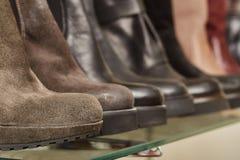 Women& de cuero x27; botas de s en los estantes en la tienda fotografía de archivo libre de regalías