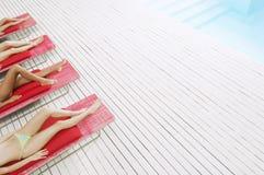 Women On Deckchairs Sunbathing By Pool stock photo