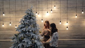 Women decorate white green Christmas tree with toys in studio stock footage