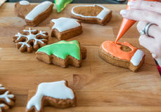 Women decorates christmas cookie Stock Images