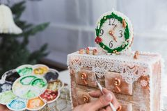 Women decorates ginger cookies Christmas chest of drawers at home. Woman draws paints on honey gingerbread cookies. Close-up stock photography