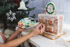 Women decorates ginger cookies Christmas chest of drawers at home. Woman draws paints on honey gingerbread cookies. Close-up royalty free stock images