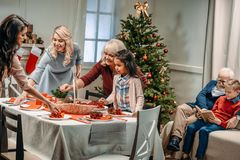 women decorating christmas table while grandfather and grandson reading book stock image