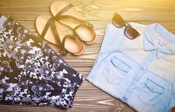 Women& x27 del verano; ropa y accesorios de s en una superficie de madera Camisa de los vaqueros, falda, gafas de sol, sandalias  Imagen de archivo