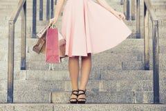 Women& delgado x27; piernas de s con las bolsas de papel Foto de archivo libre de regalías