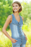 Women in denim overalls with his hands in his pockets Stock Image