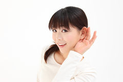 Women devote to hear the hand. Young Asian woman devote to ear the hands of white background Stock Photos