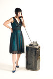 Women dialing and waiting with an stern face!. Women standing in a nice dark dress with a old rotary phone on a vintage and beat up old suitcase Stock Images