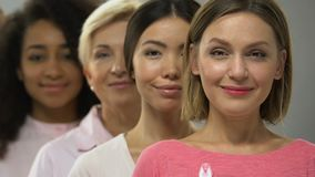 Women of different races and ages with pink ribbon, breast cancer awareness