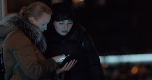 Women with digital tablet in evening street. Two women in evening city using tablet computer and discussing something stock footage