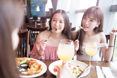 Women dine in restaurant. Beauty women smile and dine in restaurant Stock Photography