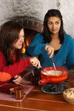 Women dipping bread into fondue Royalty Free Stock Photos
