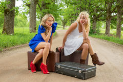 Women on dirt road sitting on the suitcases and waiting. Two women on dirt road sitting on the suitcases and waiting Royalty Free Stock Image