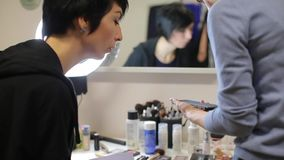 Women discuss makeup. Look, show a picture on a sheet stock video footage