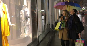Women discussing fashionable clothing outdoor. Young women having shopping evening. They holding umbrella and shopping bags while looking at show-window and stock video footage