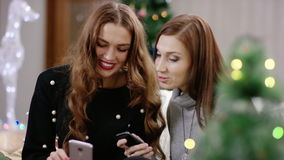 Women discussing and holding smartphone. Two women with smartphone in christmas party. Ladies looking in phone and discussing stock video footage