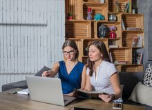 Two skilled businesswoman teamwork together with laptop computer, sitting in co-working space. Women discussion new ideas using portable net-book and web pages Royalty Free Stock Photography