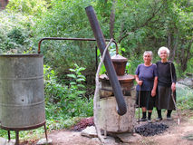 Women distilling brandy in a traditional manner. Two women distilling brandy in a traditional manner in a village in Serbia. They use an old copper kettle royalty free stock photos