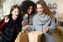 Women of diverse ethnicity with shopping bags posing in clothing store. Portrait of three smiling multiracial girls. Sharing, showing and wowing each other with Royalty Free Stock Photography