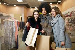 Women of diverse ethnicity with shopping bags posing in clothing store. Portrait of three smiling multiracial girls. Sharing, showing and wowing each other with Stock Photos
