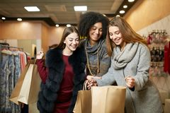 Women of diverse ethnicity with shopping bags posing in clothing store. Portrait of three smiling multiracial girls. Sharing, showing and wowing each other with royalty free stock photos