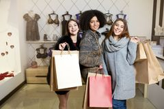 Women of diverse ethnicity with shopping bags posing in lingerie store. Portrait of three pretty multiracial girls. Walking in underwear shop on sale. Panties Royalty Free Stock Image