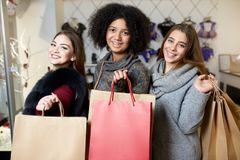 Women of diverse ethnicity with shopping bags posing in lingerie store. Portrait of three pretty multiracial girls. Walking in underwear shop on sale. Panties royalty free stock photography