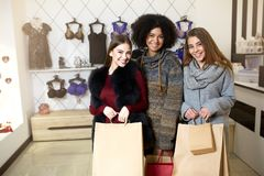 Women of diverse ethnicity with shopping bags posing in lingerie store. Portrait of three pretty multiracial girls. Walking in underwear shop on sale. Panties stock images