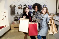 Women of diverse ethnicity with shopping bags posing in lingerie store. Portrait of three pretty multiracial girls. Walking in underwear shop on sale. Panties stock photos