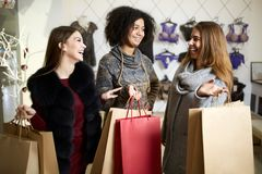 Women of diverse ethnicity with shopping bags posing in lingerie store. Portrait of three pretty multiracial girls. Walking in underwear shop on sale. Panties Royalty Free Stock Photos