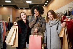 Women of diverse ethnicity with shopping bags posing in mall. Portrait of three pretty multiracial girls walking at. Lingerie and clothing store. Copyspace on Stock Images