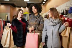Women of diverse ethnicity with shopping bags posing in mall. Portrait of three pretty multiracial girls walking at Stock Photo