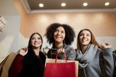 Women of diverse ethnicity with shopping bags posing in mall on sale. Portrait of three smiling multiracial girls look. Women of diverse ethnicity with shopping Royalty Free Stock Image
