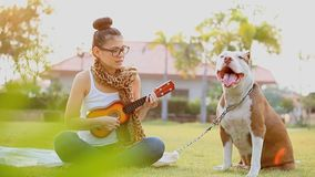 Women with dog. Women playing ukulele with dog stock video footage